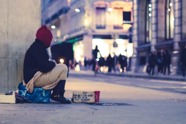 Homeless person on busy street corner