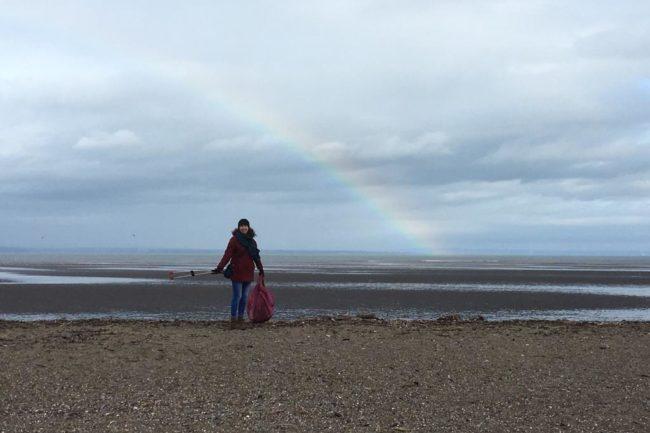 Beach cleaning under a rainbow