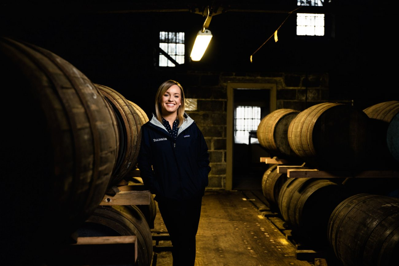 Diane leaning against whisky barrels